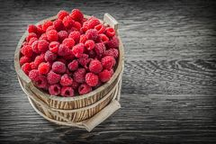 Red raspberry in bucket on vintage wooden board.  Stock Photo