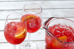 Red raspberry cold drink in glass jug and wine glasses. Red raspberry cold drink in glass jug. wine glasses and pitcher with sweet lemonade and orange slices Royalty Free Stock Photography