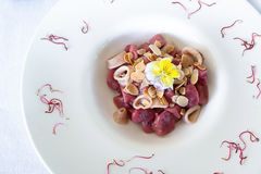Red raspberry gnocchi. With squid rings and almond fillets Royalty Free Stock Photo