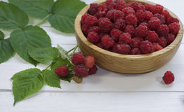 Red raspberry and green leaves. Red fresh raspberries in a wooden bowl and green leaves on a white wooden table Stock Photography
