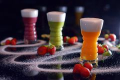 Three colorful cocktails with sugar and strawberries stock image
