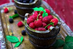 Red raspberry with leaf in a basket on vintage metal tray. Close up. Stock Photo