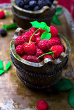 Red raspberry with leaf in a basket on vintage metal tray. Close up. Red raspberry with leaf in a basket on vintage metal tray. Close up Royalty Free Stock Image