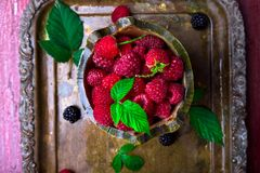 Red raspberry with leaf in a basket on vintage metal tray. Top view. Red raspberry with leaf in a basket on vintage metal tray. Top view Stock Photo