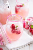 Red raspberry lemonade. Or cocktail in glasses with sugared rim stock images
