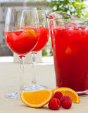 Red raspberry Lemonade pitcher and soft drink in wine glasses Stock Photos