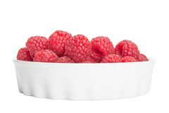 Red raspberry in a white bowl isolation. Closeup Royalty Free Stock Photos