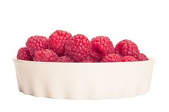 Red raspberry in a white bowl isolation. Toned in warm colors Stock Photography