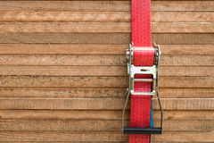 Red ratchet strap fixing wood boards / wooden planks Stock Image