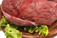 Red raw beef meat over white. Red raw beef meat and salad over white Royalty Free Stock Images