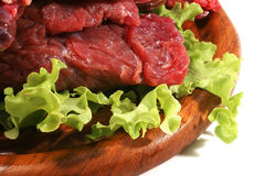 Red raw beef meat and salad. Red raw meat and salad over white Stock Photos