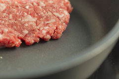 Red raw burger on a black pan close up Stock Image