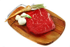Red raw meat and vegetables. On board Royalty Free Stock Image