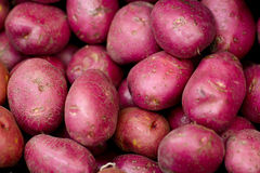 Red raw sweet potatoes. A pile of fresh vegetables is on the stall in the store Stock Photo