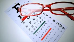Red reading glasses falling onto an eye test overhead shot. In slow motion stock video