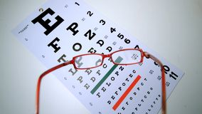 Red reading glasses falling onto eye test overhead shot. In slow motion stock video footage