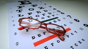 Red reading glasses falling onto an eye test. In slow motion stock footage