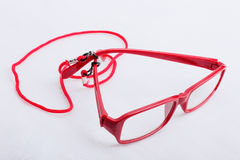 Red reading glasses with a red neck strap on a white surface Stock Photos