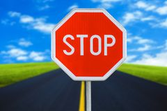 Red realistic stop road sign on blured road with sky stock photo