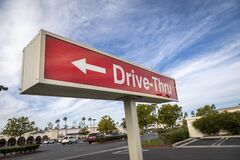 Red rectangular sign reading Drive Thru for fast food restaurant against blue sky and clouds