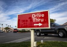 Red rectangular sign reading Drive Thru for fast food restaurant with car passing against blue sky and clouds