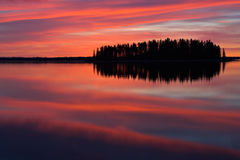Red Reflections. A blazing red sky and its reflections decorate the waters of Astotin Lake in Elk Island National Park, Alberta, Canada stock photos