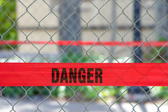 Red reflective danger barrier tape across a chain link fence Royalty Free Stock Images