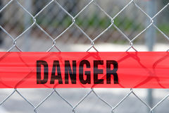 Red reflective danger barrier tape across a chain link fence Stock Images