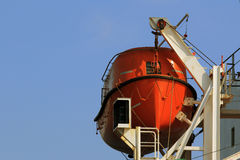 The red rescue boat on the davits of a ship on the background of blue sky Stock Photo