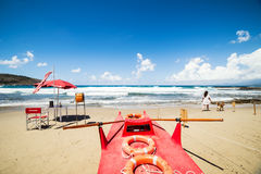 Red rescue boat, lifeguard station and girl walking with her dog on the beach Stock Photo