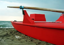 Red rescue boat with wooden oars. Along the beach Stock Photos