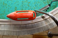 Red rescue buoy near the stairs in the swimming pool Stock Photo