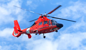 Red rescue helicopter moving in blue sky Royalty Free Stock Image