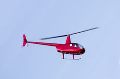 Red rescue helicopter moving in blue sky Stock Image