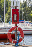Red rescue ring and dust extinguisher at the marina. stock photography