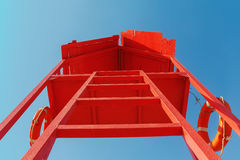 Red rescue tower with a lifeline against the blue sky Stock Photo