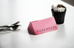 Red Reserved Signage Beside Stainless Steel Spoon and Fork on White Surface Stock Images