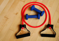 Red Resistance Band and Blue Weights on Gym Floor Royalty Free Stock Images