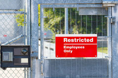 Red Restricted Employees Only Sign. And intercom / surveillance camera system CCTV on security gate entrance to a government facility Royalty Free Stock Photography