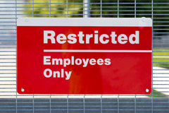 Red Restricted Employees Only Sign. On security gate entrance to a government facility Stock Photo