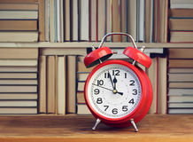 Red retro alarm clock on the background of books. Royalty Free Stock Photo