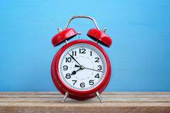 Red retro alarm clock on a blue background. Royalty Free Stock Images