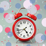 Red retro alarm clock  on a grey background. Stock Photo