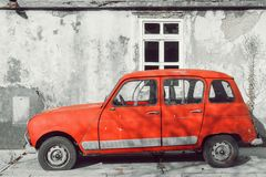 Red retro car on a background of an abandoned building Royalty Free Stock Photo