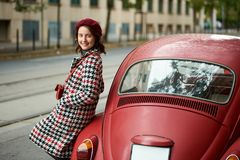 Red retro car behind and cute girl near it. Close-up. Red retro car behind and a cute girl near it. Close-up. The girl is dressed in a coat and beret with in red Stock Image