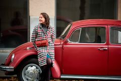 Red retro car and brunette woman leaning on him. Red retro car and and brunette woman leaning on him and looking at the distance with sweet smile. Urban life Stock Image
