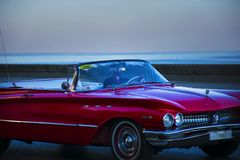Red retro car on the Malecon seafront in blue glow. Luxury red retro car on the Malecon waterfront on a background of the ocean Royalty Free Stock Photos
