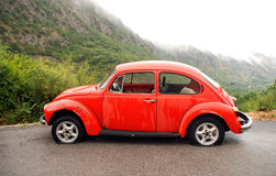 Red retro car on a mountain road Stock Images