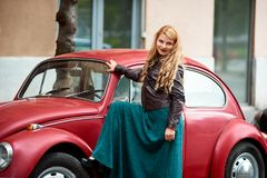 Red retro car near blonde girl with long curls. Red retro car and near blonde girl with long curls. Female in a long dress has put her foot on the wheel of a car Stock Photo