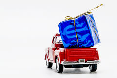 Red retro car pickup with a blue gift box isolated Royalty Free Stock Image